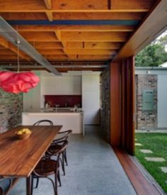 A sliding glass wall separates the dining room from the small backyard. The floor is polished concrete and references the humble materials of the original structure.   Photo by Brett Boardman.