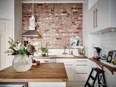 brick in kitchen as accent wall. subway tiles. fan over stove. wood island…