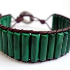 This simple bracelet is woven from some beautiful malachite, and brown leather and then finished off with small silver coloured button.