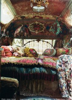 Caravan bedroom, gypsy style. Walls covered with lovely rugs, and antique bed frame and harmony all over the bed, rounds pillows with rugged silk, patterns, crochet attachments, and awesome lamps to give a romantic look.