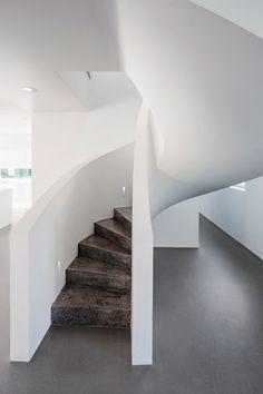 A sculptural white staircase lit by a skylight connects an open-plan living space to a mezzanine floor inside this house in Finland