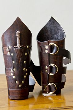 Elaborate bracers held closed with three leather belt strips, includes small dagger in a riveted pocket. Available in any color.