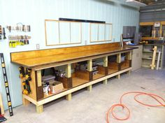 Finished shop work bench with shelving & storage insets. Bench top finish is Minwax Golden Oak stain and 5 coats of Minwax gloss polyeurethane. Trim is 3/4 or 1/2 inch Poplar stained with Minwax Dark Walnut. Framing on wall is for two 2x4ft pegboards.
