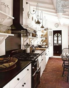 color palette: terracotta floor tiles and creamy white walls/kitchen cabinets with black accents