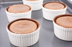 A photo of hot chocolate fondants in white ramekins on an aluminum cookie sheet.