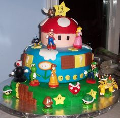 Smoochies Creations - 19th Birthday Super Mario themed cake. Bottom and middle tiers are chocolate orange cake with chocolate orange cream cheese and whipped cream icing. For the filling I used orange flavoured vanilla pudding. Top tier (mushroom part) is a vanilla rainbow cake with coconut flavoured buttercream icing. Characters are from the Mario chest set which was part of the present.