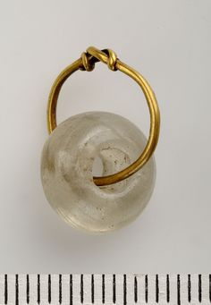 Viking age clear glass bead hanging on a gold wire - Birka Grave 523, Sweden.