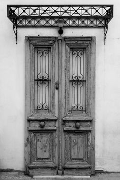A fake blue door decorates a parking. Doors, Black And White, Nature, Blue, Home Decor, Fotografia, Black White, Homemade Home Decor, Blanco Y Negro