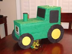 John Deere tractor pinata.  I cut it out from a diaper box and used green crepe paper to cover it.  Added on the wheels, smoke stack etc.  Crepe paper to cover all green and black surfaces with extra tag/poster paper for the windows and wheel centers.  Pulled JD logo off of Web and printed out.  Made a cutout in the bottom with a trap pull-string door if needed.
