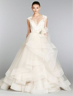 This ball gown features a sweetheart neckline with a natural waist in tulle and lace. It has a chapel train and cap sleeves. Our floor sample is on sale! We only have one available in a size 12