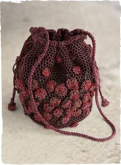 A veritable work of art, densely crocheted and over-embroidered with wine-dark netting and dimensional rosebuds. Accented with glass beading, braided tassels and a thick braided strap. Fully lined, with small inside pocket.