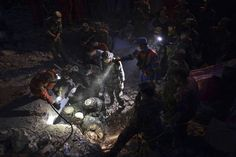 Paramilitary policemen use flashlights to search for the body of a boy, buried under the debris, at night after an earthquake hit the Longtoushan township of Ludian county, Yunnan province, August 5, 2014. REUTERS/Stringer