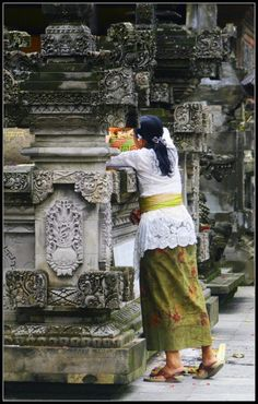 Balinese placing an offering at the Tirta Empul Temple.