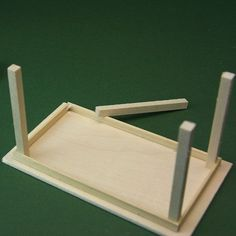 Glueing the legs into the corners of a simple dolls house miniature kitchen table.