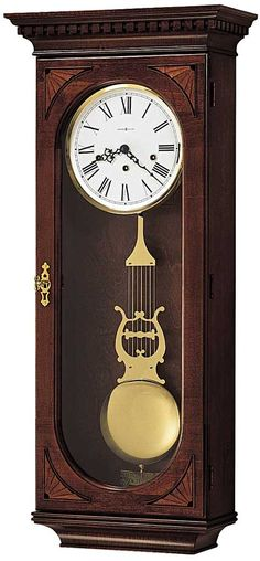 """This wall clock features a distinctive dental molding on the profiled pediment with maple and ebony hand-rubbed marquetry overlays at each corner. The white dial offers black Roman numerals. A brass lyre pendulum appears behind the locking door. Finished in Windsor Cherry on select hardwoods and veneers. German made Key-wound, Westminster chime movement with hour count. Triple chime movement plays Westminster, Whittington or St. Michaels. Size: H. 33-1/2"""" W. 14-1/2"""" D. 6-3/4"""""""