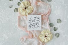 """#Inspirational quote Inspirational quote """"The greater your storm the brighter your rainbow"""" written in calligraphy style on paper with dry white tulips eucalyptus petals and pink textile on concrete background. Flat lay composition for social media magazines bloggers and artists. This purchase includes one high resolution horizontal digital image. Image is a sRBG jpg and is approximately 4108x2739 pixels. License terms: http://ift.tt/1W9AIer"""