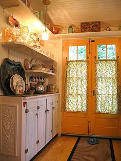 A set of antique French doors are painted marigold orange, via Flickr LOVE the color. What a happy color.