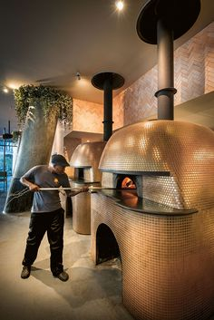 Two gigantic imported Stefano Ferrara pizza ovens, widely considered the Rolls-Royce of pizza ovens, are open to the restaurant. They have been clad ingold mosaics to add a theatrical aspectto the experience of dining at Saint. Pizzeria Design, Bar Restaurant Design, Pizza Restaurant, Restaurant Kitchen, Oven Design, Design Café, New Pizza, Four A Pizza, Outdoor Kitchen Bars
