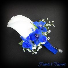 A white full-size rose accented with dark blue delphinium, fresh babies breath, green leaves, and royal blue chiffon stem wrap.  ~ Boutonniere designed by Pamela's Flowers ~ Find us online at www.pamelasflowers.net