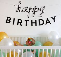 Fill the crib with balloons for first birthday photo shoot.