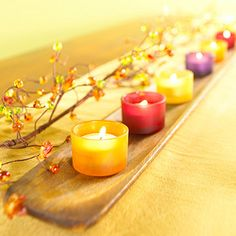 Colorful votive cups paired with fall branches make a table pop with color. See more simple Thanksgiving centerpieces: