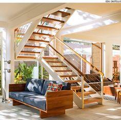 Para não pesar no living, faça uma escada vazada com estrutura metálica e degraus de madeira maciça. No guarda-corpo, coloque cabos de aço estendidos abaixo do corrimão. Projeto do escritório Arkitito.