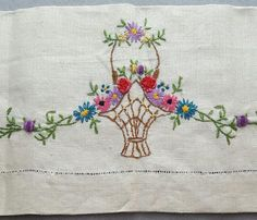 Linen tea towel in antique white with superb embroidery of a basket of flowers. Measures: 22-1/2 inches X 15-3/8 inches from finished selvage to