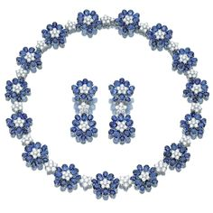 SAPPHIRE AND DIAMOND DEMI-PARURE Comprising: a necklace designed as a series of flower head motifs set with oval sapphires and brilliant-cut diamonds, spaced by brilliant-cut stone clusters, length approximately 430mm, together with a pair of pendent earrings en suite, post and clip fittings, all mounted in white gold, pochette.