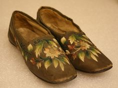 "Pair of child's shoes. Brown leather exterior with silk embroidery across body of floral design - pink flowers, multi-tone green leaves. Black leather piece at heel for reinforcement. Lined with plain linen. Brown silk ribbon sewn around edge of opening of shoe. Leather sole. 7"" long x 2"" wide x 2"" high"