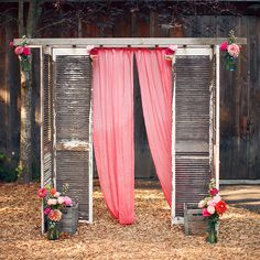 A rustic wedding altar made of weathered shutters and gauzy pink fabric, complete with colorful flowers, created by Barbs Flowers.