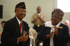 Turner G. Blount, one of the first African American Marines, and Louise Greggs, a representative from the national Montford Point Marines Museum, stand in a room of servicemembers during the 2nd Medical Battalion, 2nd Marine Logistics Group Black History Month celebration aboard Camp Lejeune, N.C., Feb. 15, 2013. Montford Point Marines such as Blount fought through the barriers of racism to serve in the military during World War II.