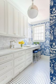 A long laundry room features a Hicks pendant over walls clad in David Hicks The Vase Wallpaper in Blue lined white shaker cabinets adorned with nickel hardware paired with honed white marble countertops and a carrera marble subway tiled backsplash. Laundry Room Wallpaper, White Laundry Rooms, White Shaker Cabinets, Cocinas Kitchen, Hill Interiors, Sweet Home, Laundry Room Design, Transitional Decor, Transitional Kitchen