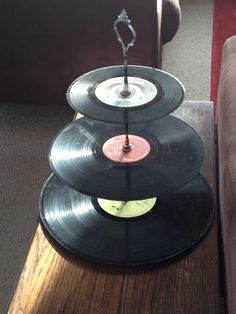 Re-using old records to make a cake stand is a creative idea, especially for a party where a love for music once played on a record is shared.