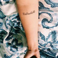 """Unbreakable"" tattoo on Anastasia's forearm."