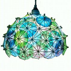 GREAT idea. Hanging plug-in paper lantern I could find for cheap @ IKEA + attach colorful paper cocktail umbrellas. Seems easy - must try.