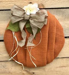 This is a handmade orange burlap pumpkin wreath with small hydrangea like flower, raffia, and brown/burlap ribbon