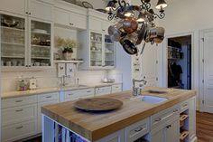 White cabinets, quartz countertop, island with butcher block counter