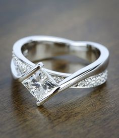 Twenty round cut diamonds are pave set in this elegant half bezel diamond bridge engagement ring in white gold, accenting a kite-set princess center diamond.