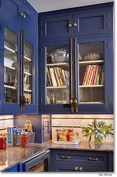 Beautiful blue butler's pantry with glass-front uppers and cremone bolts