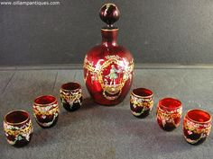 Attributed to Josef Riedel Bohemian Cranberry Liqueur Set (1914-1921) This is a gorgeous little hand painted and gilded cranberry liqueur set comprising of a carafe and six glasses