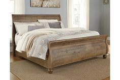 Trishley queen sleigh bed is farmhouse-inspired style done to perfection. It's beautifully crafted of solid pine wood, enriched with knotty character and natural saw marks. Distressed light brown finish has a touch of gray for gently weathered charm. Curved headboard and footboard are adorned with planking. About $1K