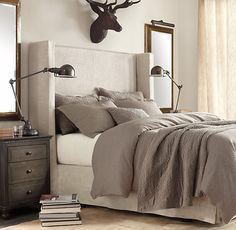 I actually kind of love this monochromatic bedroom with a high-rise upholstered headboard and Restoration Hardware's Rust Stag Head.
