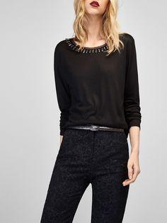 Camiseta con detalle de cuello joya, confeccionada en tejido 100% viscosa. Corte recto, cuello redondo y manga larga.