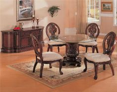 Dine in the elegance of the round glass top dining table and chair set. The table features a glass top with an elegantly sculpted base, while the four dining side chairs have a sculpted back and legs with an upholstered seat cushion. Add the dining buffet and hutch for a complete collection.