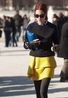 Taylor Tomasi Hill in yellow tulip skirt, dark grey tights, blue clutch, navy&dark grey pullover & sunglasses