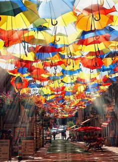 Umbrellas Street, Portugal. From July to September hundreds of colorful umbrellas float above the shopping promenades of Agueda, Portugal as part of the local Agueda Art Festival. #streetart