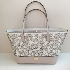 "Kate Spade Small Margareta Model: WKRU 3793. Beautiful tote features white laser cut flower design with leather bottom . Open top with dog leash type closure. Dual handles of about 8.5"" drop . Comes with pouch .Interior : signature lining, zipper pocket, multifunction pockets. Pebble/cream colors kate spade Bags Totes"
