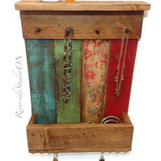 This is a colourful, rustic, wood jewelry organizer with a 4 top shelf and a deep bracelet box along the bottom. This beautiful organizer has 4 wood pegs for plenty of necklaces, and gold eyelets for earrings along the front. Painted with blue, red and greens, distressed, trimmed in a medium stain and protected with a satin finish. The backside is adorned with 2 metal keyhole brackets for an easy hang. Display all your bling in style!  Measures 16x13x4deep Do you need a bigger size? Just…