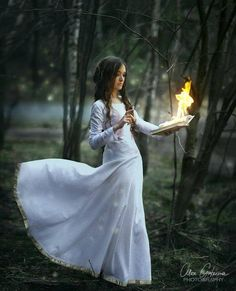 I've always wanted to have this kind of photoshoot! a white dress in a burnt forest with smoke swirling around... eerily beautiful. Except, you know, without the burning book and instead a candle or lantern or something haha :)