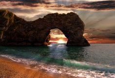 Sunrise through Durdle Door sea arch in Dorset, Jurassic Coast